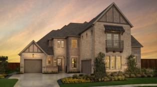 Two-story brick home with a three-car split garage.  Cedar trim accents and a second story balconly add detail to the front of the home.
