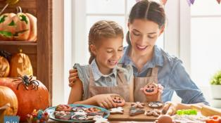 Mother and her daughter preparing homemade treats for Halloween
